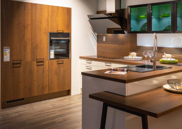 Ausstellungsküche kaufen Saarland - Holz und weiß mit angebautem Tisch